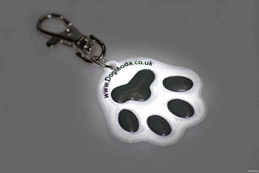 Large reflective dog paw dangler tag reflects light in the dark