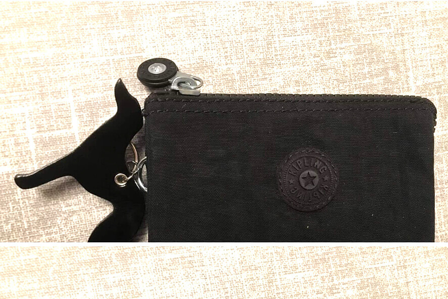 Black whippet key ring used as a bag charm on lady's purse